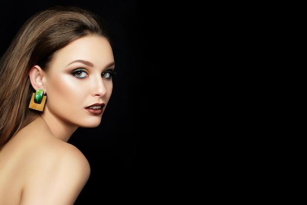 黒い背景の上に茶色の唇と緑のスモーキーな目を持つ若い女性の肖像画を閉じます。