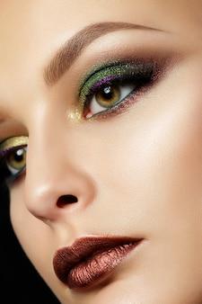 茶色の唇と緑のスモーキーな目を持つ若い女性の肖像画を閉じます。完璧な眉毛。現代のファッションが構成しています。