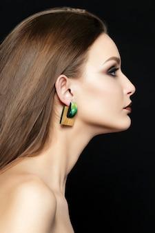 갈색 입술과 녹색 스모키 눈을 가진 젊은 여자의 초상화를 닫습니다. 완벽한 눈썹. 현대 패션 메이크업.