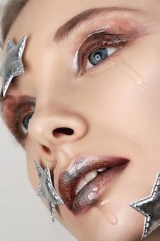 창의적인 메이크업으로 젊은 여자의 초상화를 닫습니다. 우는 작은 별. 액체 유리, 금속 반짝이 및 스모키 눈.