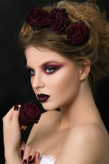 Крупным планом портрет молодой женщины с темно-фиолетовым партийным макияжем, держащей темно-красную увядшую розу