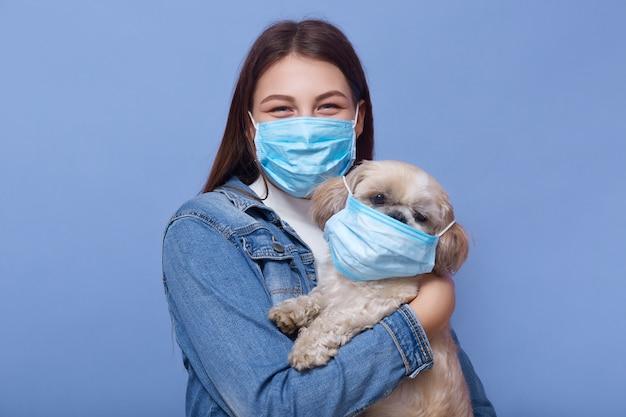 長い髪の若い女性の肖像画をクローズアップ、デニムジャケットとメディカルマスクをドレスします。ウイルスの蔓延に対する予防策として、サージカルマスクを手に彼女の犬を保持しています。コロナウイルスのパンデミックのコンセプト。