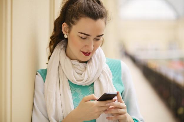 携帯電話で若い女性の肖像画をクローズアップ