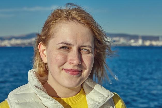 붉은 머리와 그녀의 입술에 약간의 미소를 가진 젊은 여자의 클로즈업 초상화
