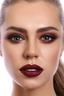 Закройте вверх по портрету молодой женщины с винно-красными губами и бронзовыми дымчатыми глазами. макияж современной моды.