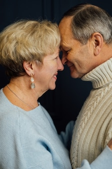 Close up portrait of old couple wife and husband smiling. dark blue background. happy lovers on