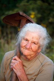 Close-up portrait of an old woman with gray hair smiling and looking at the camera, holding a rusty shovel in her hands, face in deep wrinkles