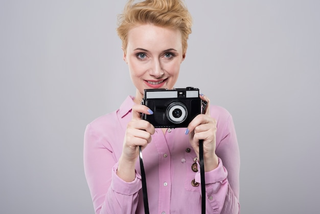 오래 된 카메라를 들고 젊은 여자에 초상화를 닫습니다
