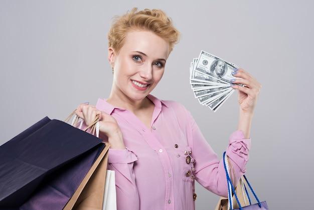 ショッピングバッグとお金を保持している若い女性の肖像画を閉じる