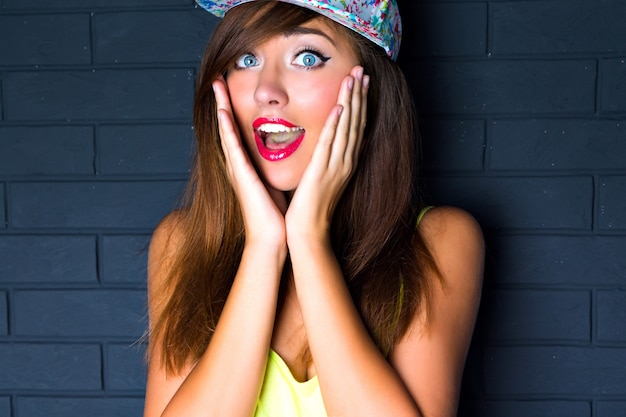 Close up portrait os sexy smiling woman, laughing out her hands to the cheeks surprised emotions, bright make up, long hairs swag retro hat. bright toned colors.