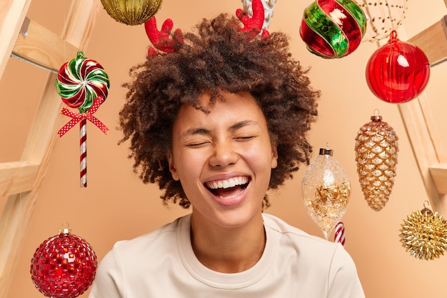 Close up portrait of overemotive curly haired woman with broad smile shows white teeth wears red reindeer horns dressed casually