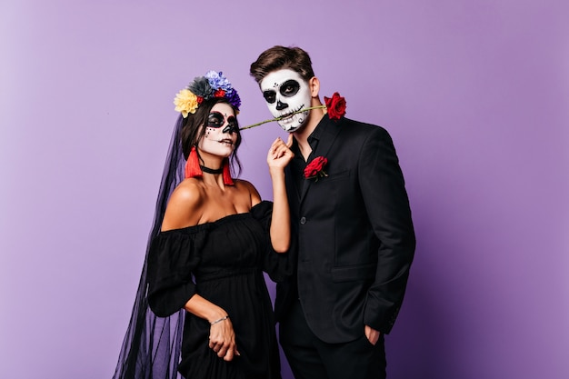 Close-up portrait of pair of lovers in festive carnival costumes posing on purple background. passionate mexican man holds rose in his teeth while his bride looks into camera.