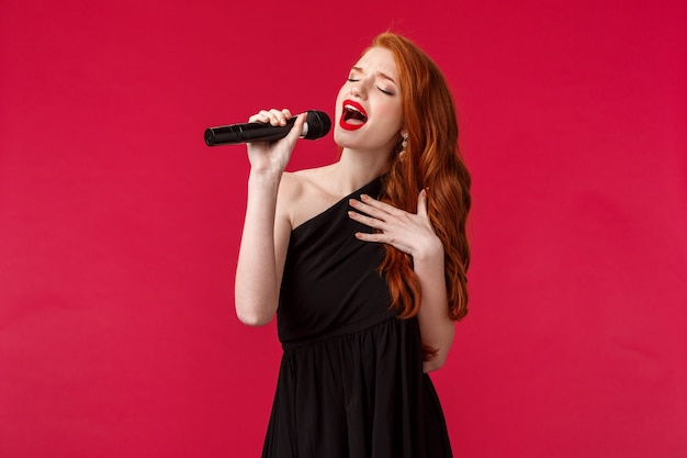 Close-up portrait of passionate beautiful female singer perform songs, wearing black evening dress, close eyes and showing her feelings through music, hold microphone, attend karaoke on girls night