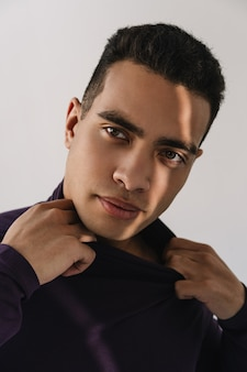 Close up portrait of pensive african american man with emotional face wearing stylish purple turtleneck