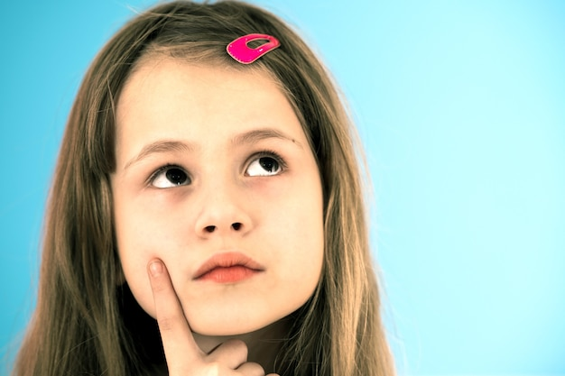 Close up portrait of pensive cute little girl with pink hairpin on blue background. concept of childish dreams.
