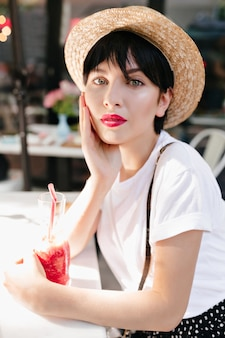 Close-up portrait of pensive girl with gray eyes and red lips resting in cafe with glass of icy beverage