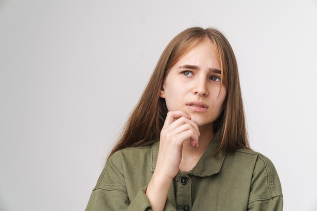Close up portrait of a pensive pretty young girl with long blonde hair standing