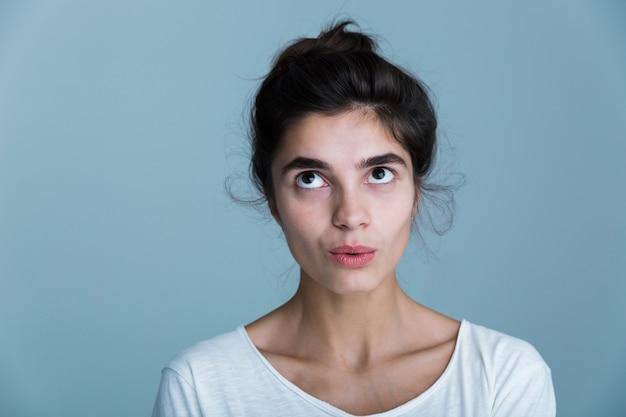 Close up portrait of a pensive unsatisfied pretty young brunette woman wearing white t-shirt standing isolated over blue background