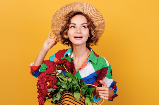 Close up portrait of pensive woman with curly hairstyle with bouquet of pions in hands. yellow  wall background.