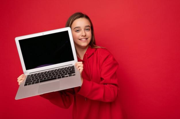 コンピューターのラップトップを保持している赤いパーカーを着て長い髪の美しい幸せな笑顔の女の子のクローズアップの肖像写真