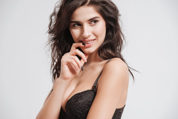 Close up portrait of a playful sexy woman wearing bra and looking away isolated