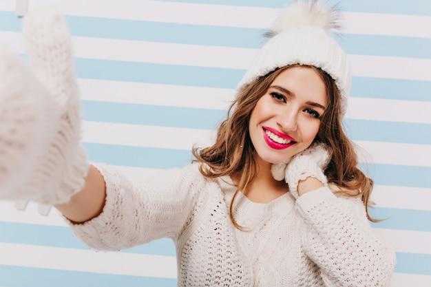 Ritratto del primo piano della ragazza bruna positiva in guanti di lana carino facendo selfie sulla parete a strisce. ridendo signora con cappello bianco e guanti lavorati a maglia che si prende una foto.