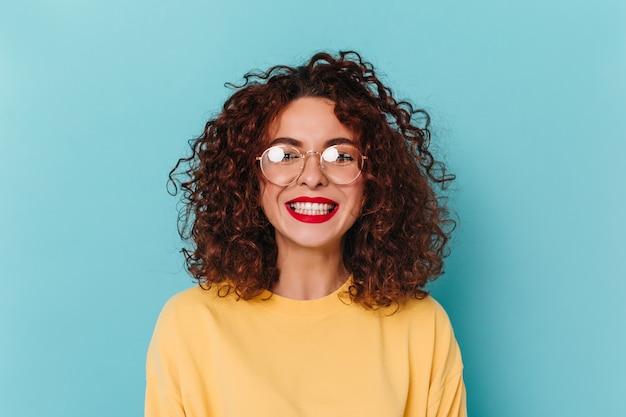 Ritratto del primo piano della ragazza positiva, dai capelli scuri e ricci con gli occhiali. la donna con il rossetto rosso vestita in felpa gialla ride di tutto cuore contro lo spazio blu.