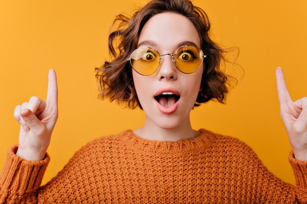 Close-up portrait of positive european woman wears elegant yellow sunglasses.  enchanting curly girl expressing surprised emotions.