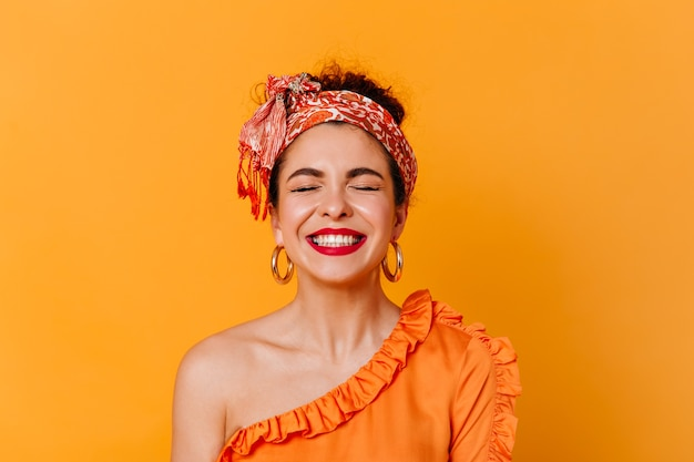 Close-up portrait of positive woman with red lips dressed in blouse with bare shoulder and headband laughing with closed eyes on isolated space.