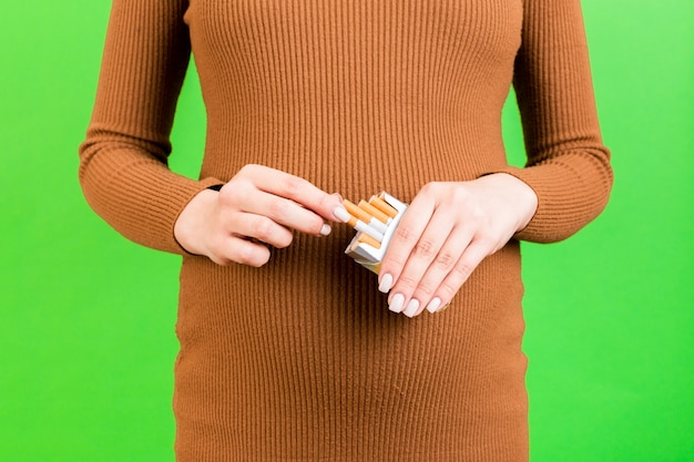 Close up portrait of pregnant woman in brown dress holding a pack of cigarettes at green background. harmful habit during pregnancy.