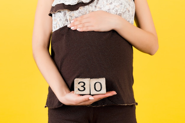 Close up portrait of pregnant woman in brown pajamas showing cubes with thirty weeks of pregnancy against her belly at yellow background. baby expecting. copy space.