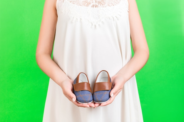 Close up portrait of pregnant woman in white dress holding booties for baby boy at green background. happy child expecting. copy space.