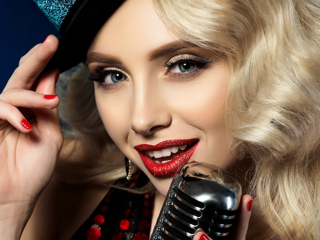 Close up portrait of pretty blond female singer holding retro styled microphone