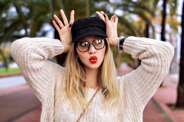 Close up portrait of pretty blonde woman wearing trendy casual outfit , red lipstick and clear glasses, manicure and jewelry, surprised emotions, posing on the street with palms, travel alone.