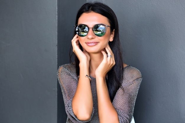 Close up portrait of pretty brunette woman with tanned skin and long hairs posing near gray wall, wearing casual sweater and sunglasses.