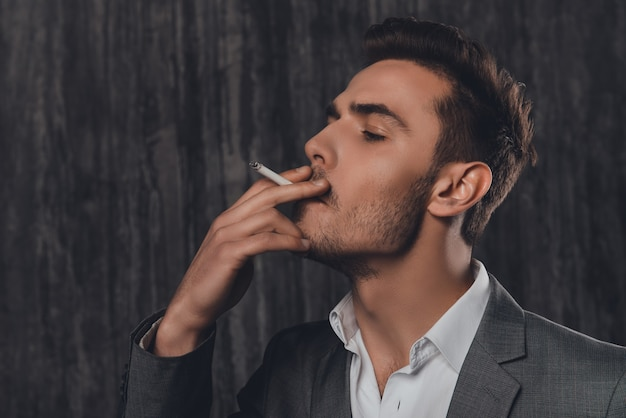 Close up portrait of pretty businessman smoking a sigarette