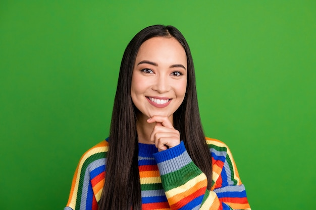 Close-up portrait of pretty content cheerful girl wearing striped pullover touching chin isolated over bright green color background
