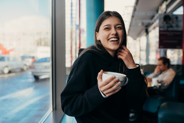Close up portrait of pretty female drinking coffee. lady holding a white mug with hand.