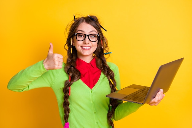 Close-up portrait of pretty funky cheerful girl holding in hands laptop showing thumbup advert isolated bright yellow color background