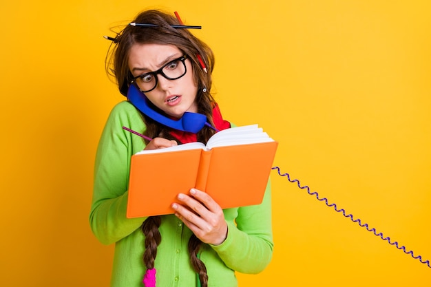 Close-up portrait of pretty funky worried girl talking on phone writing home task isolated bright yellow color background