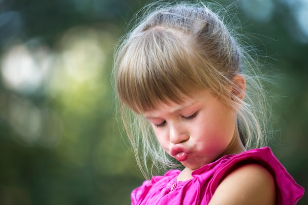 Close-up portrait of pretty funny moody young blond preschool child girl in pink sleeveless dress feeling angry and unsatisfied on blurred summer green copy space . children tantrum concept.