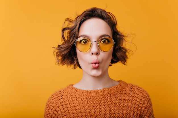 Close-up portrait of pretty girl isolated on yellow space with kissing face expression