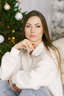 Close-up portrait of a pretty girl sitting near a christmas tree and lights