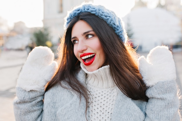 Close-up portrait of pretty girl with black long hair posing with hands up in cold day. outdoor photo of cute european lady in blue hat and white gloves enjoying winter weekend.