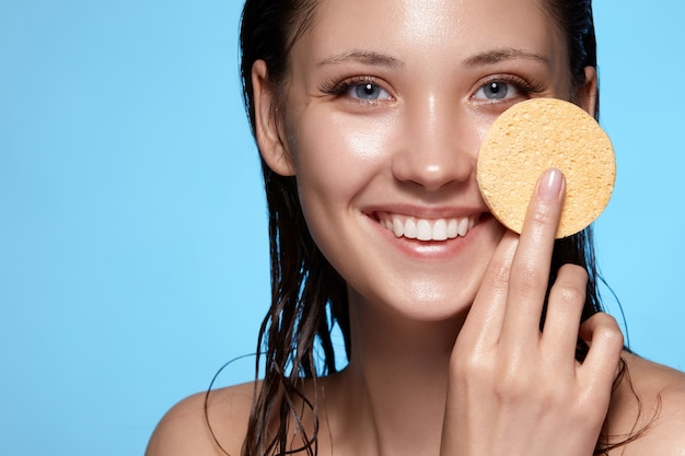 Close-up portrait of pretty girl with wet hair washing face with beige sponge and smiling