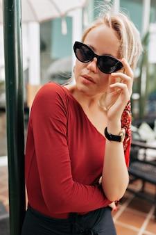 Close up ritratto di bella signora che tocca i suoi occhiali da sole all'esterno