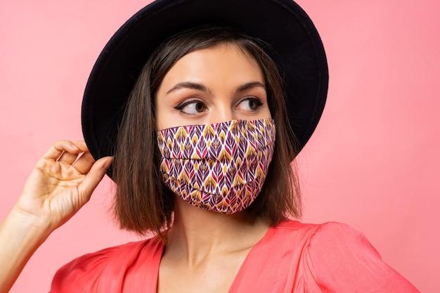 Close up ritratto di bella donna vestita elegante maschera protettiva. indossare cappello nero e occhiali da sole. in posa sul muro rosa