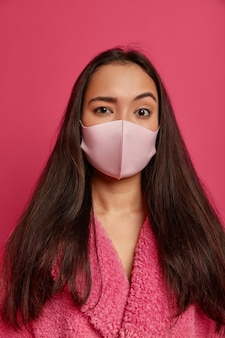 Close up portrait of pretty young woman wearing a protective face mask isolated