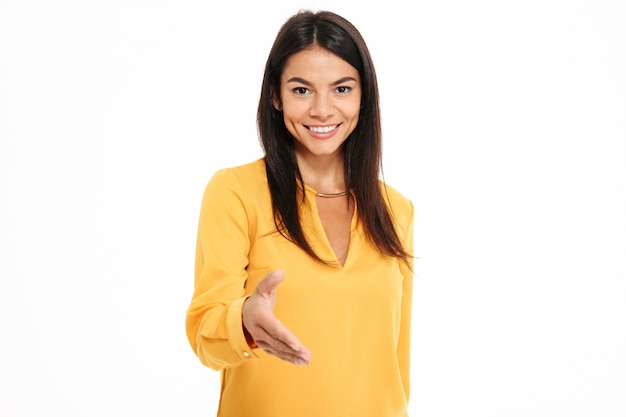 Close-up portrait of pretty young woman in yellow shirt holding out her hand to greet someone