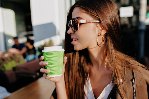 Close-up portrait  profile of cheerful caucasian woman in glasses drinking coffeet on city background.